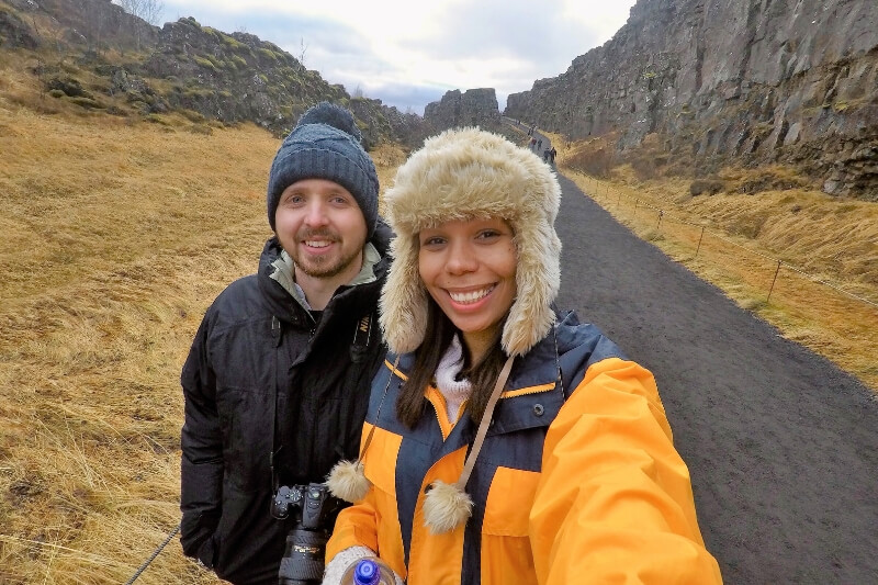 Man wearing sdark blue hat and black waterproof coat and woman wearing bright yellow jacket and fluffy crem hat standing on a path in a valley in Iceland in November