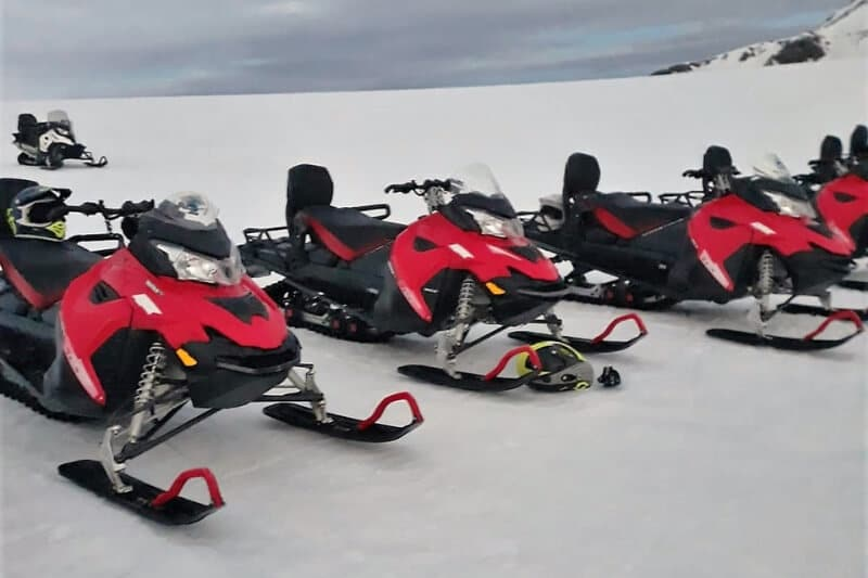 Red and black snowmobiles on a glacier in Iceland