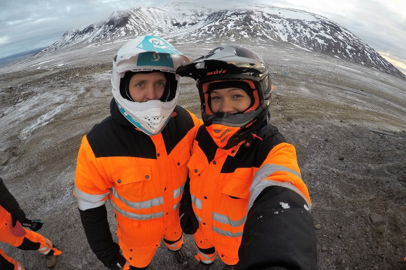 Man and woman wearing orange all-in-one suits and helmets in front of a mountain range