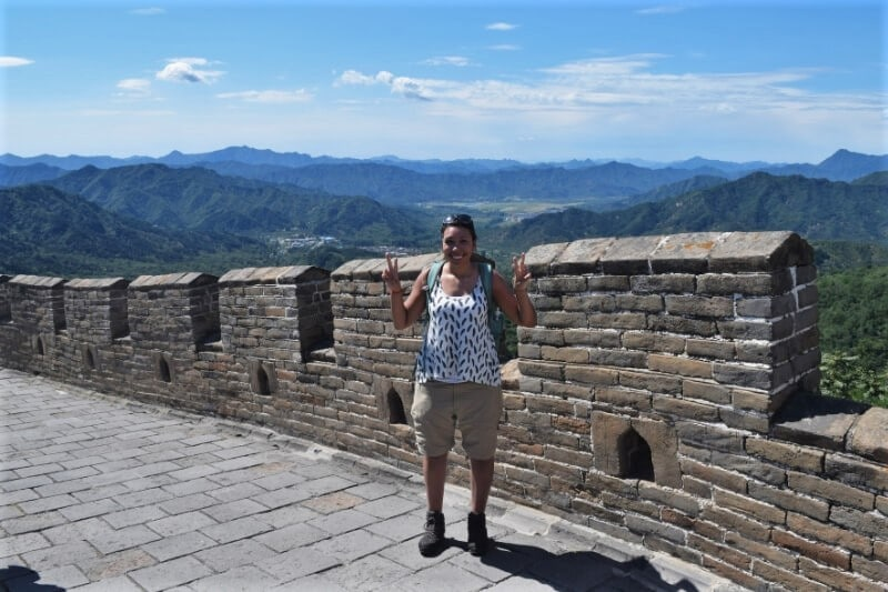 Girl with red backpack wearing shorts doing peace sign on Beijing Great Wall