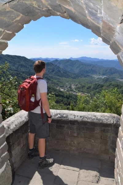Man with red backpack standing looking out over the Great Wall of China