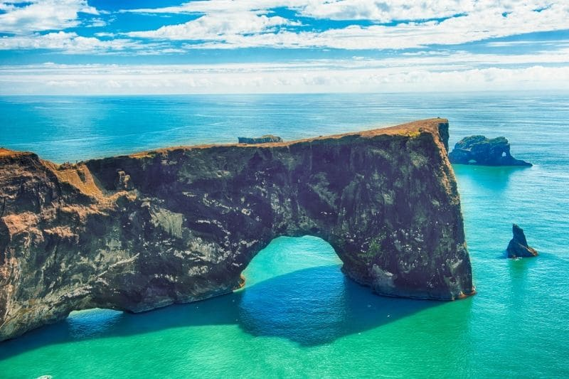 A natural arch spanning into the sea on one of the best Iceland Beaches