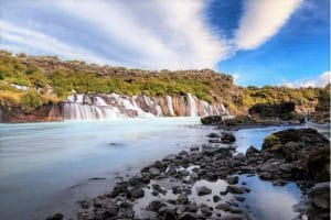1km wide waterfalls with blue sky and clouds and rocks in the foreground