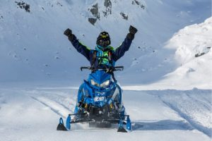 Person on a blue snowmobile on the snow with their arms up in the air