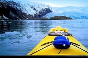 Yellow kayak siting on water in front of glacier
