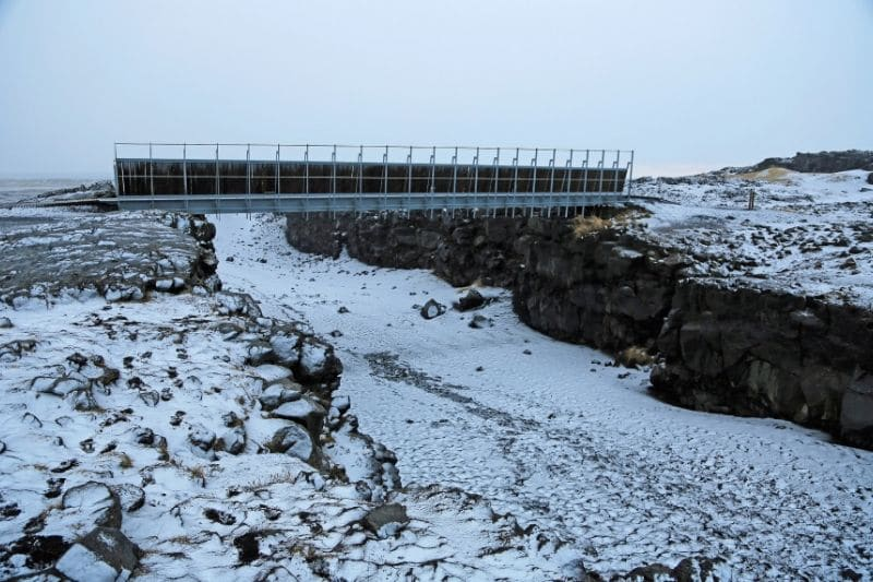 A bridge that goes over an Iceland beach separating two continents