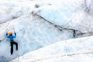 Person climbing up a glacier with ice axes