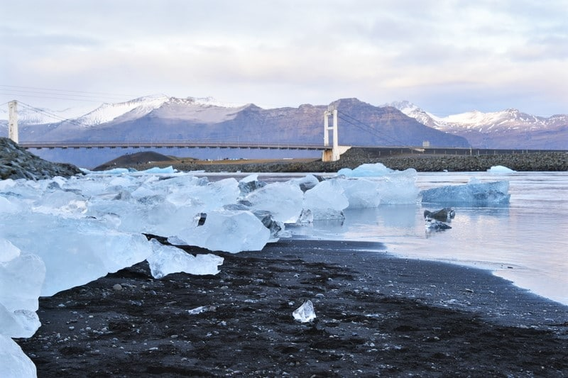 Large ice crystals on a black sand beach with bridge in the background