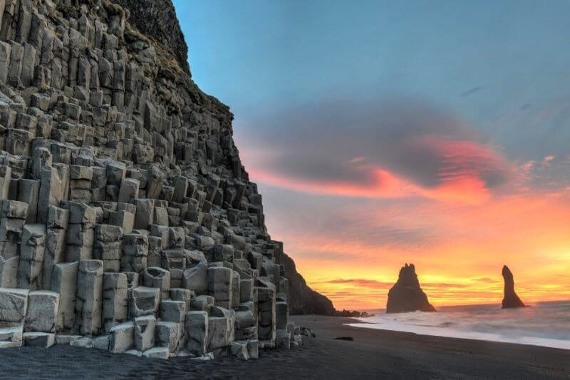 Black ragged cliffs with pink and yellow sunset on the right
