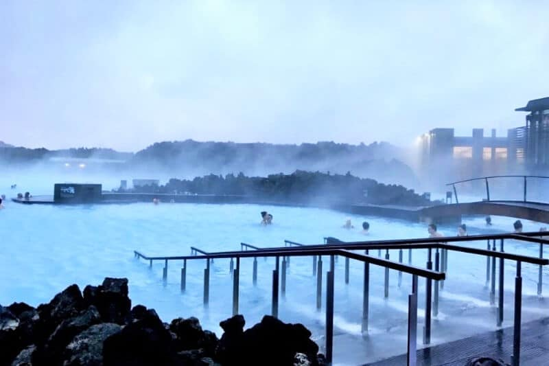 handrail going into milky blue waters with steam coming from lagoon