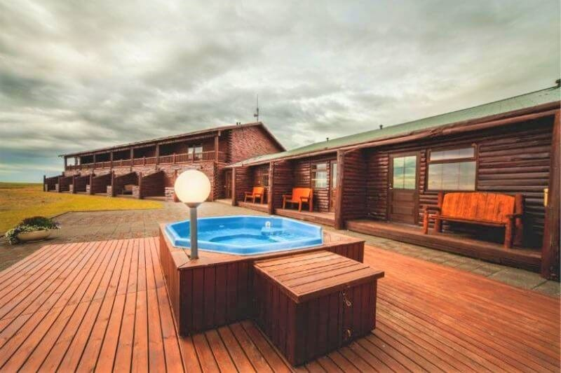 Hot tub on wooden decking outside a wooden log hotel