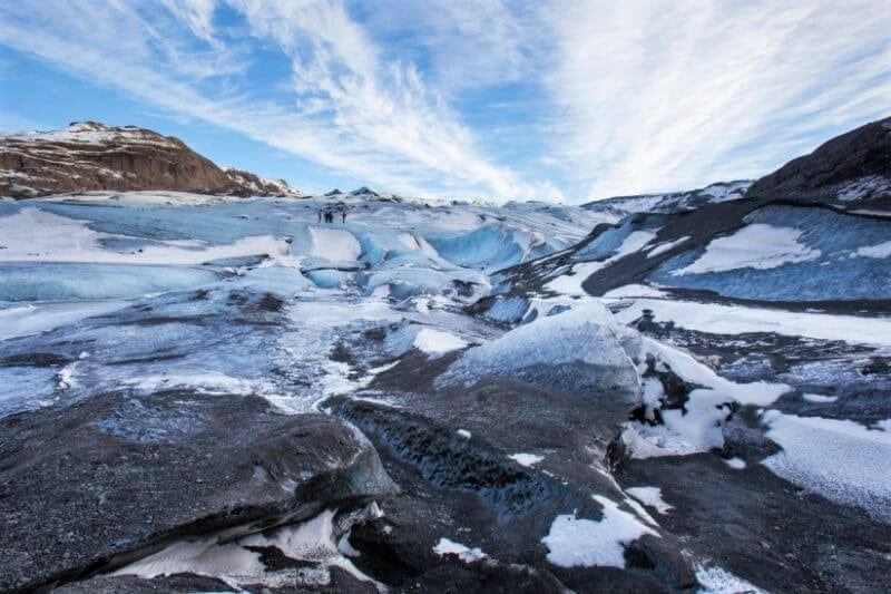 The top of a glacier with broken ice and black sand showing through