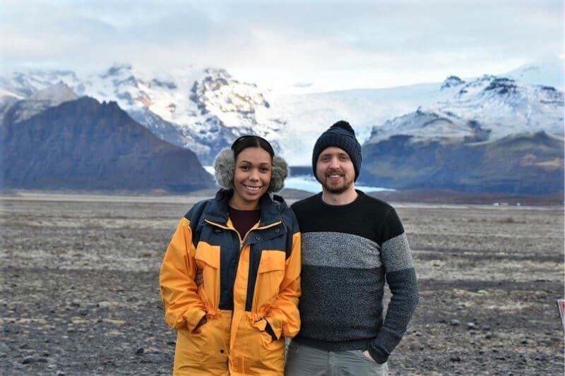 a girl wearing a yellow raincoat and grey earmuffs and a man standing next to her wearing a grey and black jumper and a blue woolly hat in front of snow capped mountains