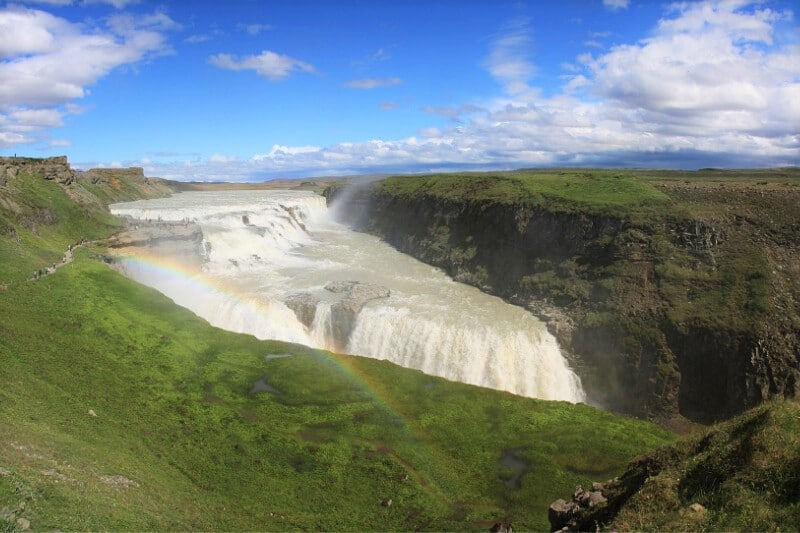 green cliffs separating with a huge triangular waterfall falling in between, and a rainbow near the front