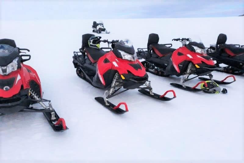 4 red and black snowmobiles on the white ice