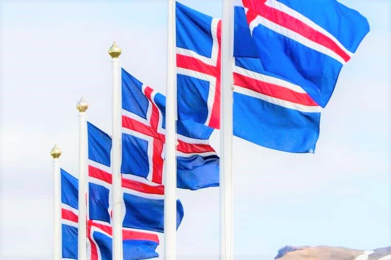 5 Icelandic flags on poles - blue backgrounds with red and white cross