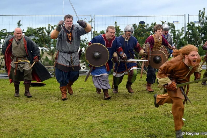 7 men dressed in medieval clothes and weapons running angrily towards the camera