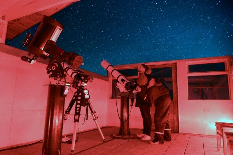 night time at a unique hotel in Iceland - red lighting on 2 people looking into a telescope with dark blue sky and stars