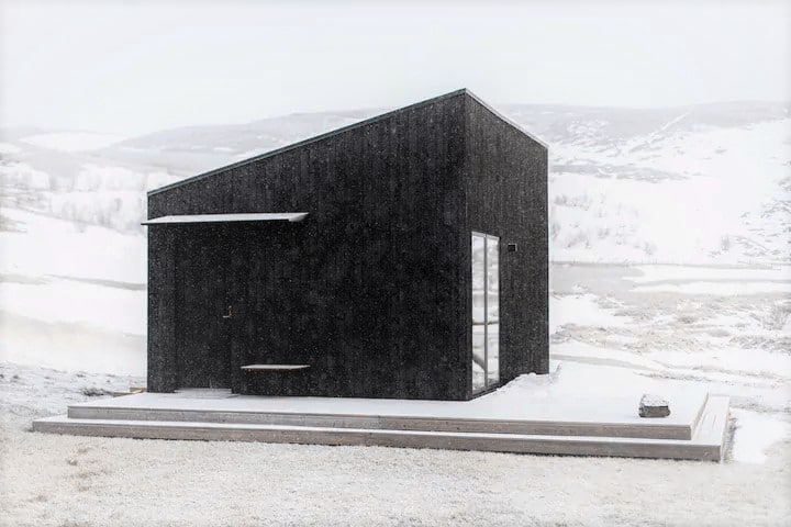 Small square black building surrounded by snow and mountains in the background