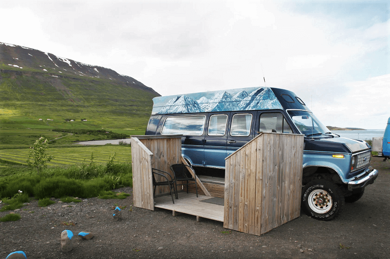 Vintage blue van with small sundeck attached with mountains in the background