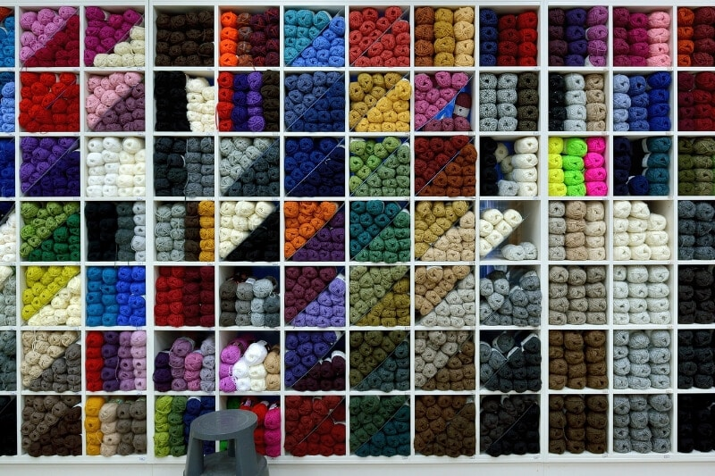 Large shelf with lots of different yarns in the boxes