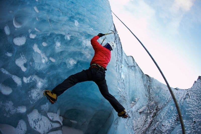 A man climbing up a glacier with ice climbing equipment on a tour in Iceland in winter