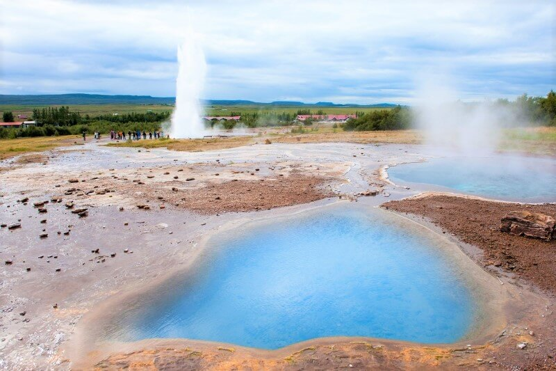 Blue pool of water with erupting geyser in background