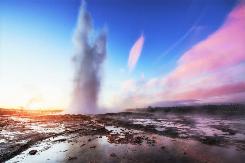 Strokkur geyser erupting with water 30m in the air, pink and blue sky