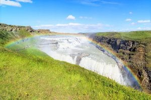 Gullfoss waterfall cascading into a canyon blue skies, green grass surrounding it with a rainbow