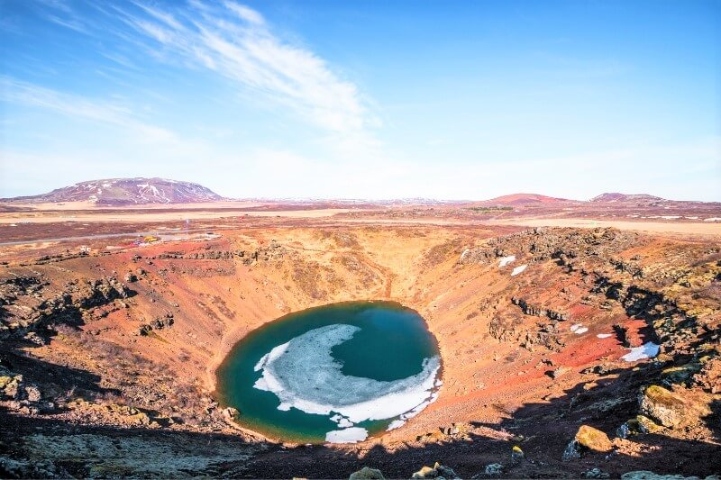 Blue lake in crater surrounded by red rock