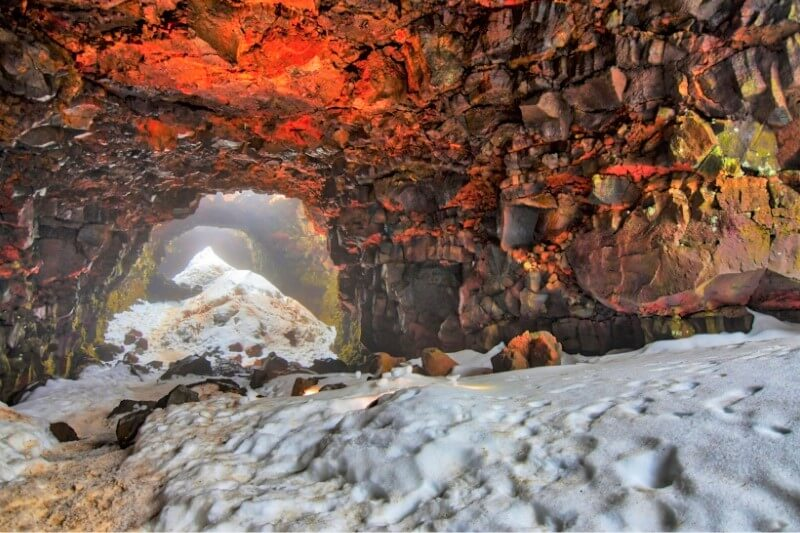Raufarhólshellir Lava Tunnel with red roof and grey stone on the bottom