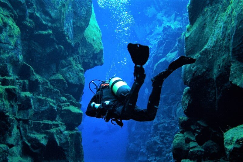 Silfra tectonic plates with one diver in between swimming away