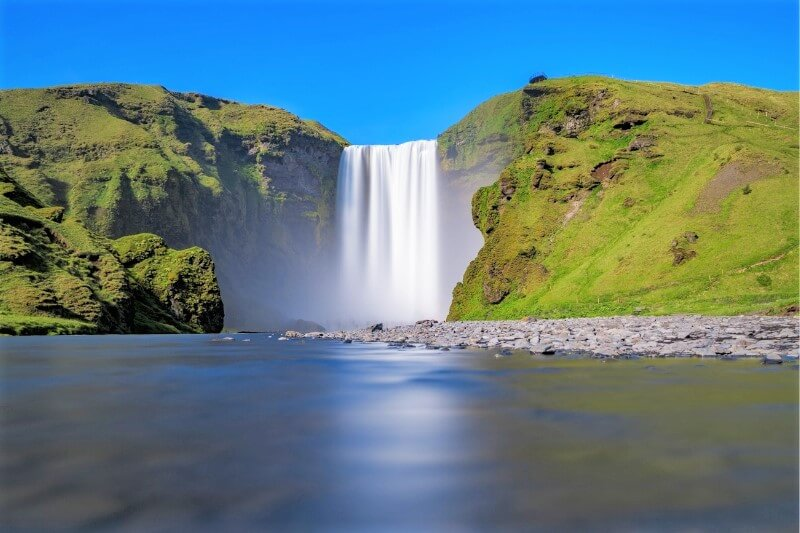 Skogafoss waterfall rushing down with lake in foreground and blue sky