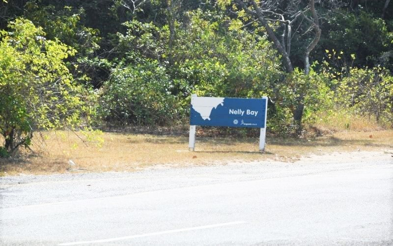 Green bushes with blue roadside sign saying Nelly Bay