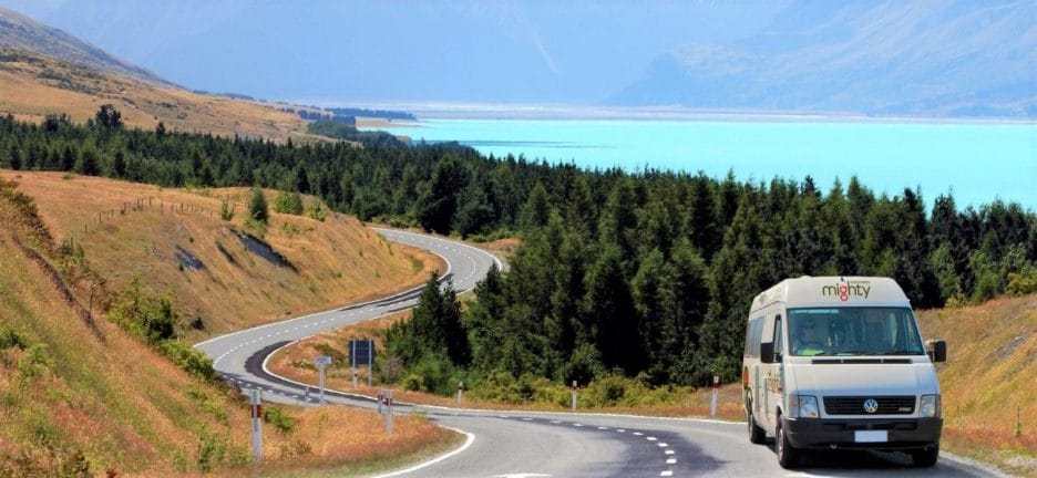 Van Life Essentials: Campervan driving along winding roads with bright blue lake and green pine trees in background