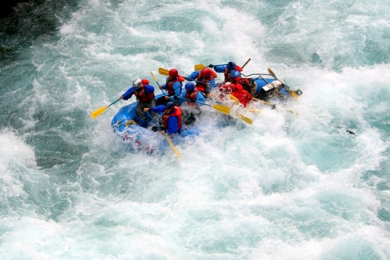 Group of people white water rafting in frothy water