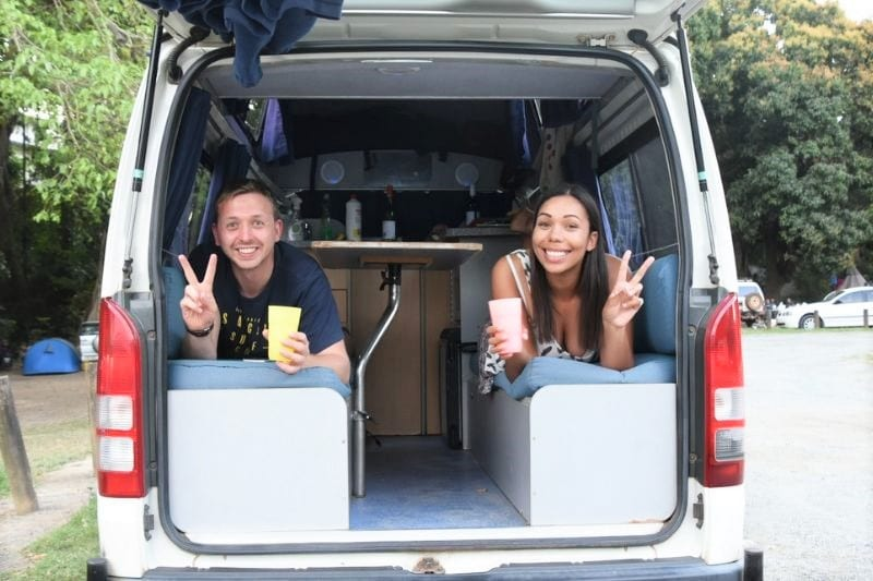 Man and a woman lying in a converted campervan with the back door open doing the peace sign