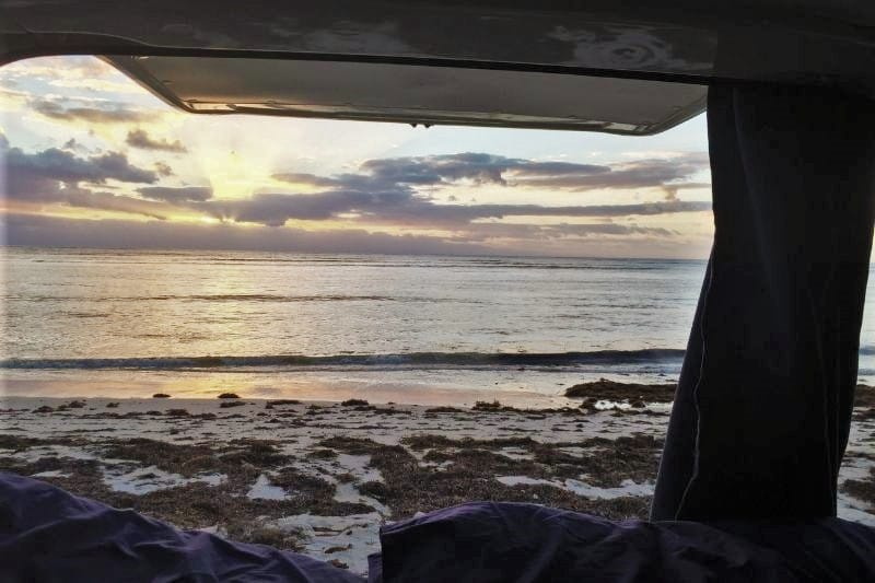 View from inside of a campervan with yellow and pink sunset at the beach