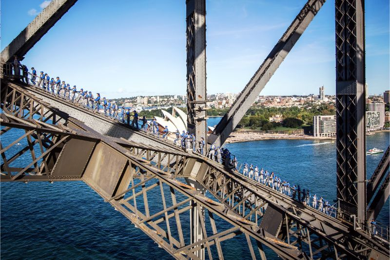At least 60 people climbing up the metal on the Sydney Harbour Bridge