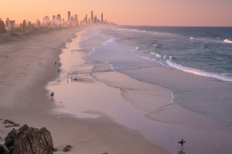 Sunset view of Surfer's Paradise with ocean on the right and beach on the left with city skyline in the background