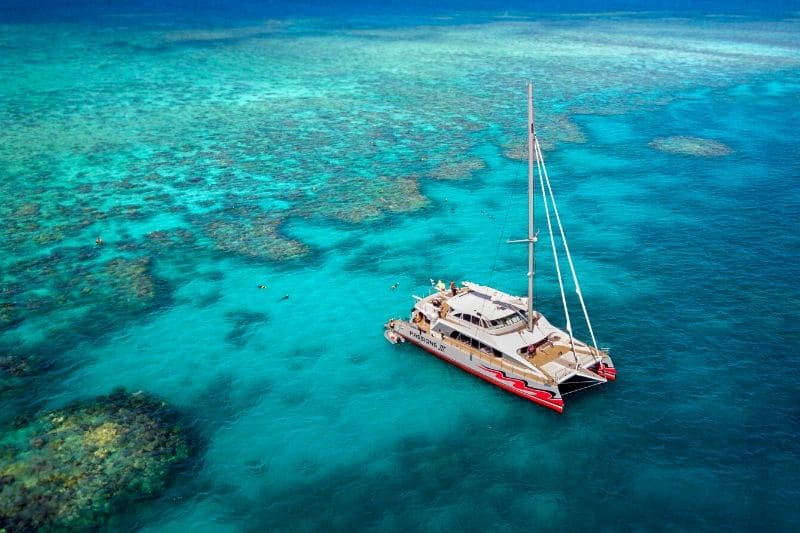 Air view of a catamaran in the waters overs the Great Barrier Reef, Australia