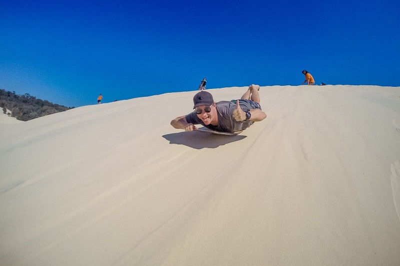 A man sandboarding on Moreton Island with a thumbs up to the camera