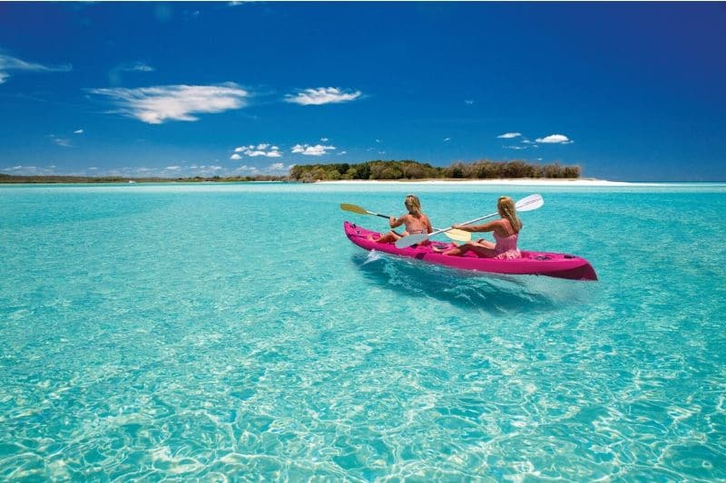 2 blonde women in a pink kayak with clear blue water and small island with trees in the background