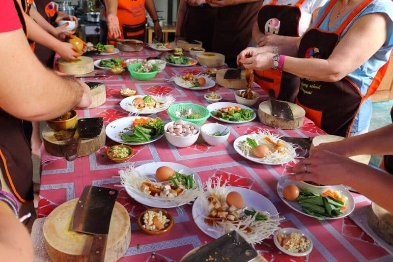 Lots of people gathered round a chiang mai cooking school table