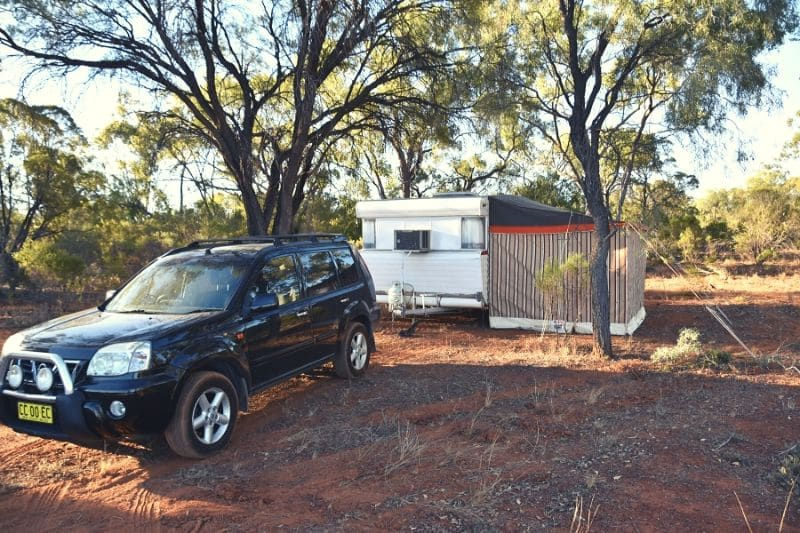Black Nissan X-Trail parked up with a caravan and awning in a campsite