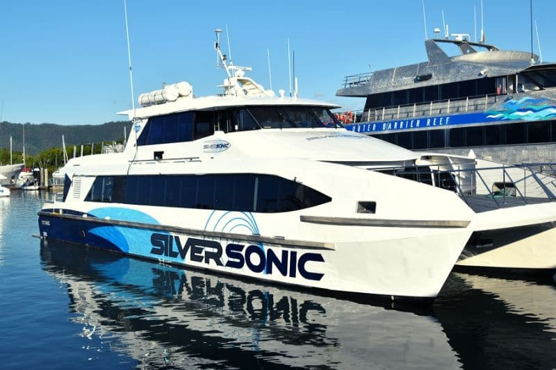 White catamaran in the dock with blue words along the side saying Silversonic