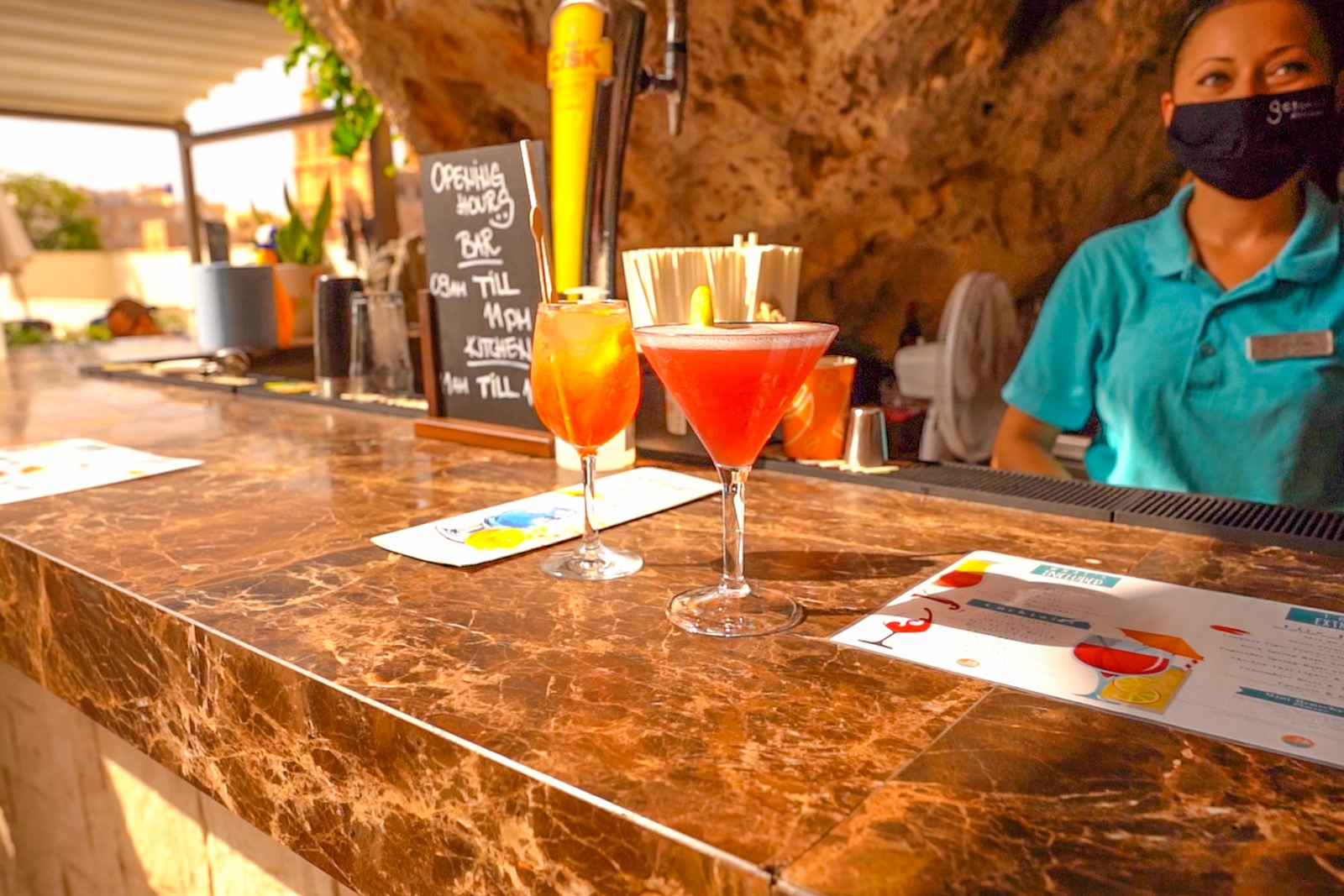 Orange cocktail in tall wine glass and red cocktail in small triangular glass on a bar