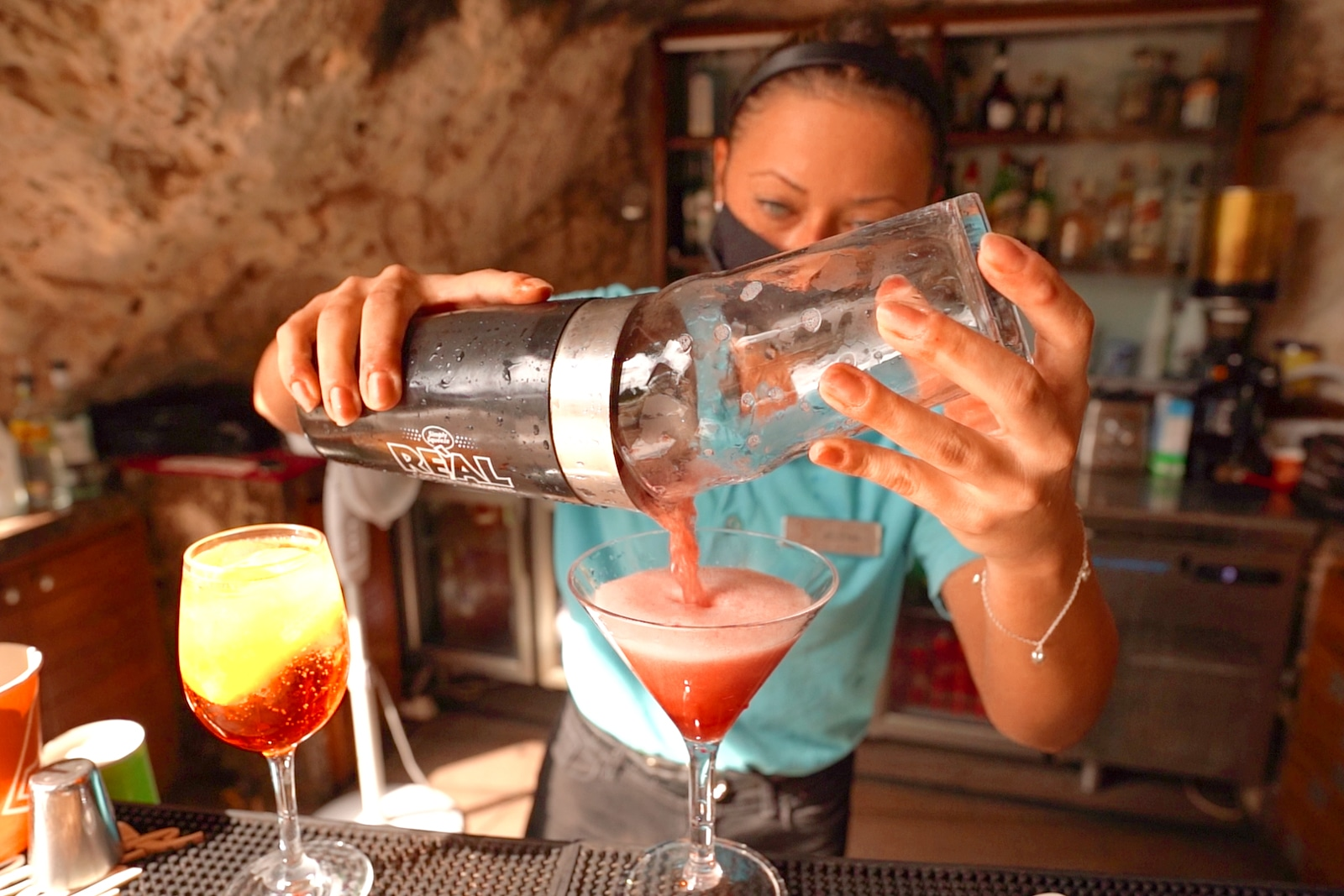 Woman pouring red cocktail into glass