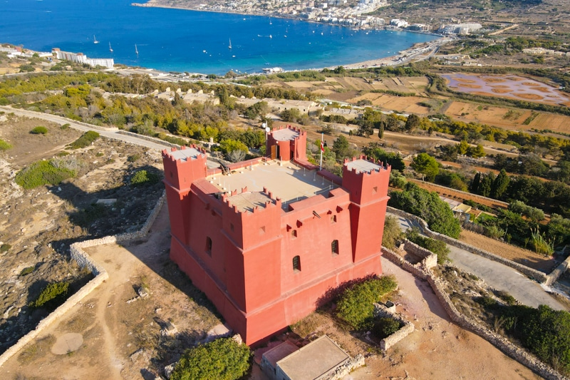 A far away drone shot of the Red Tower with Mellieha bay in the background