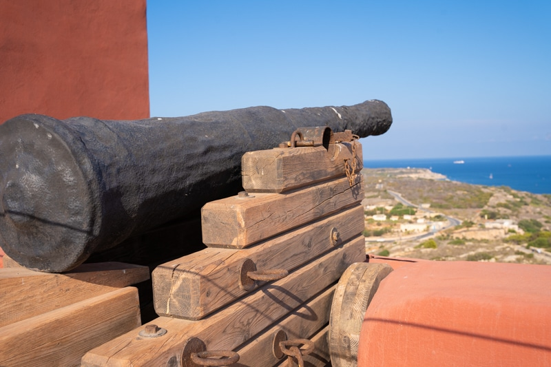 A canon facing out to see on top of the Red Tower